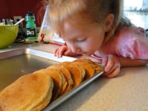 Female child smelling whole wheat banana pancakes on kitchen counter.