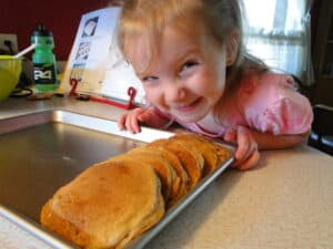 Female child grinning big at pan filled with whole wheat banana pancakes.