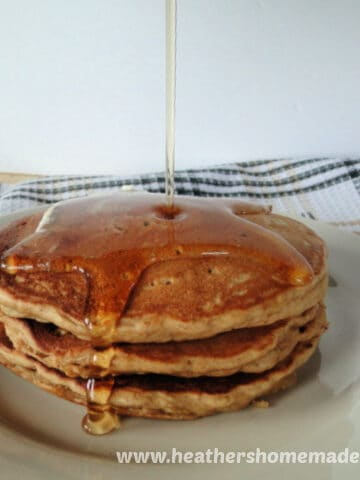 Stack of 3 Whole Wheat Banana Pancakes with drizzle of syrup on white round plate.