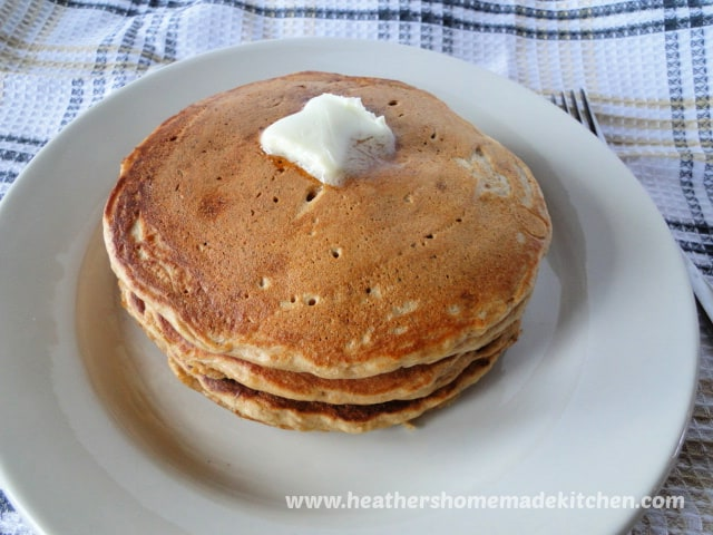 Whole Stack of 3 Wheat Banana Pancakes with pat of butter on top on white round plate.
