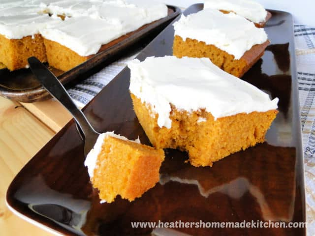 Front view of Pumpkin Bars with Cream Cheese Frosting with bite on fork on brown platter.