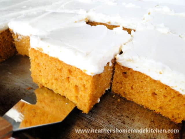Pumpkin Bars with Cream Cheese Frosting slice on spatula in sheet pan.