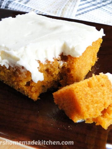 Close up view of Pumpkin Bars with Cream Cheese Frosting with bite on fork on brown platter.
