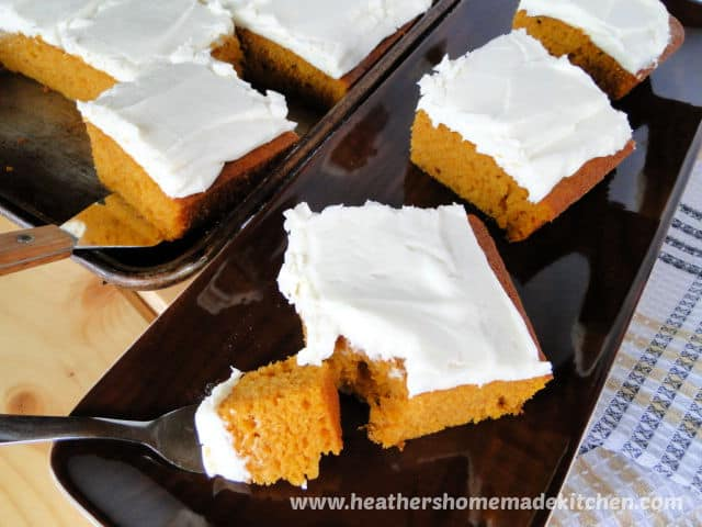 Pumpkin Bars with Cream Cheese Frosting with bite on a fork on a brown platter.