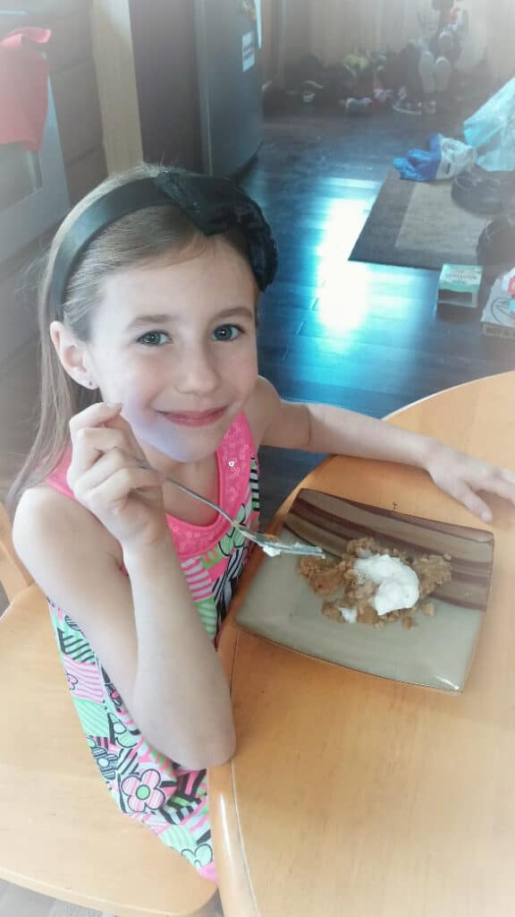 Girl sitting at table with fork in hand and apple crisp on plate.