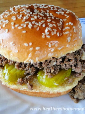 Iowa Maid Rites with pickles and loose meat spilling onto white round plate.