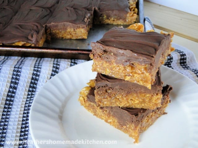 Scotch-a-roos cut into bars and stacked 3 high on round plate in front of bars on sheet pan.