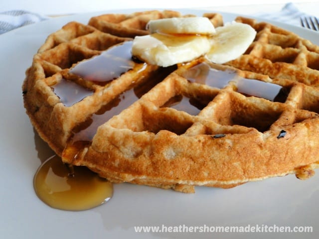 Close up of Banana Belgian Waffles with sliced bananas and syrup on top.