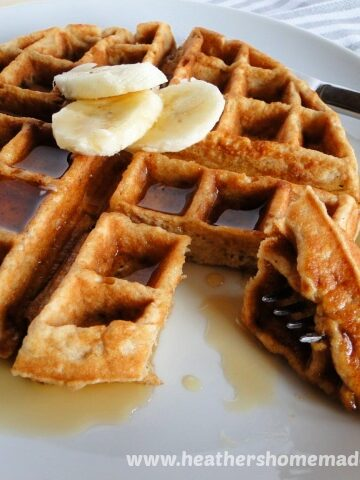 Banana Belgian Waffles with sliced bananas and syrup on white plate and a bite on a fork.