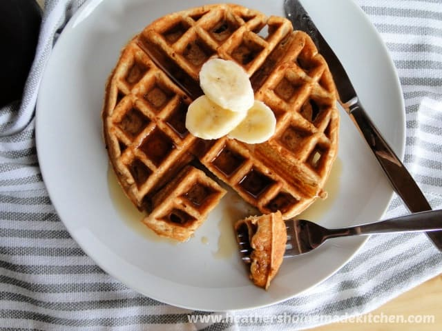 Top view of Banana Belgian Waffles on white plate with bite of waffle on fork.