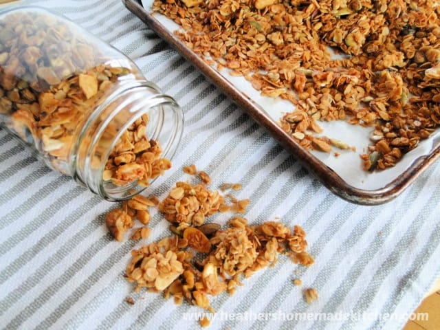 Homemade Granola in jar, some on table and sheet pan.
