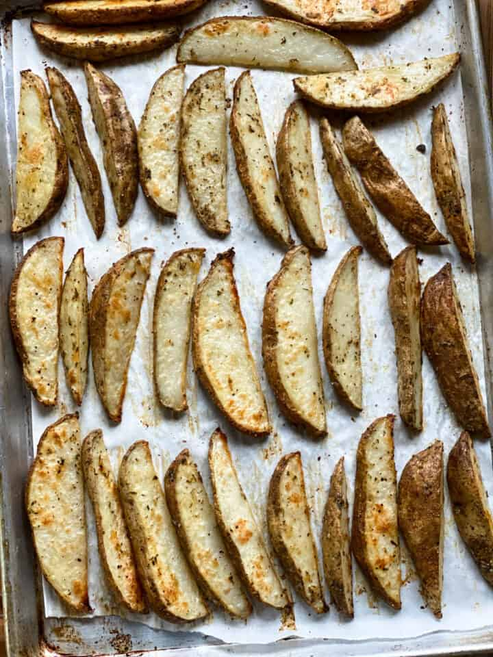 Baked crispy oven fries on sheet pan ready to be served.