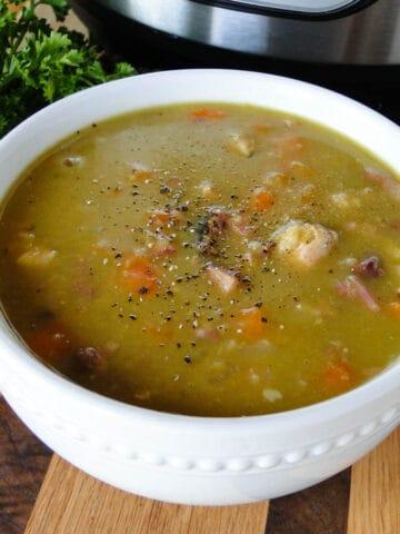 Instant pot split pea soup in white bowl.