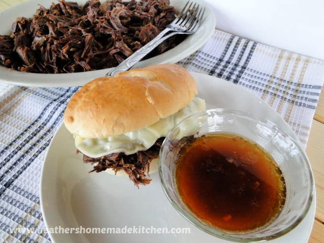 Instant Pot Drip Beef Sandwiches on plate with bowl of au jus and platter of shredded beef behind.