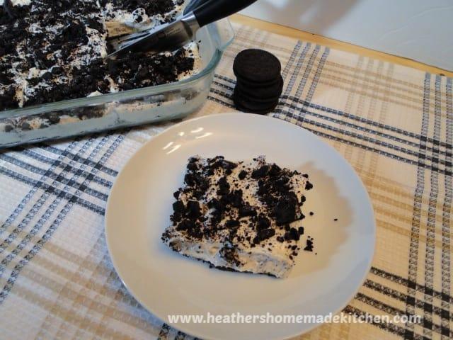 Slice of No Bake Cookies N' Cream Cheesecake Bars on plate.
