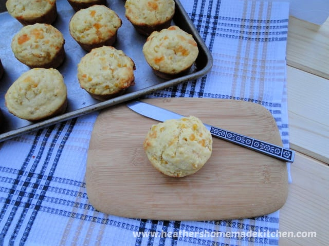 Sheet pan of Cheesy Corn Muffins with on a board with butter knife.