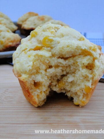 Close up view of Cheesy Corn Muffins with bite taken out of one muffin sitting on a board.