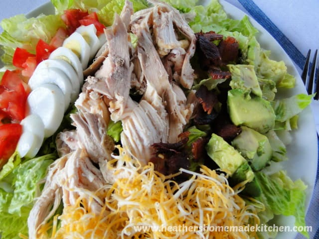 Roast Chicken Cobb Salad with bacon pieces, avocado, shredded cheese on white plate.