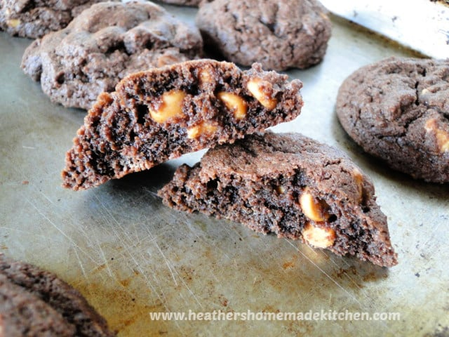 Peanut Butter Chip Chocolate Cookies broken in half on sheet pan.