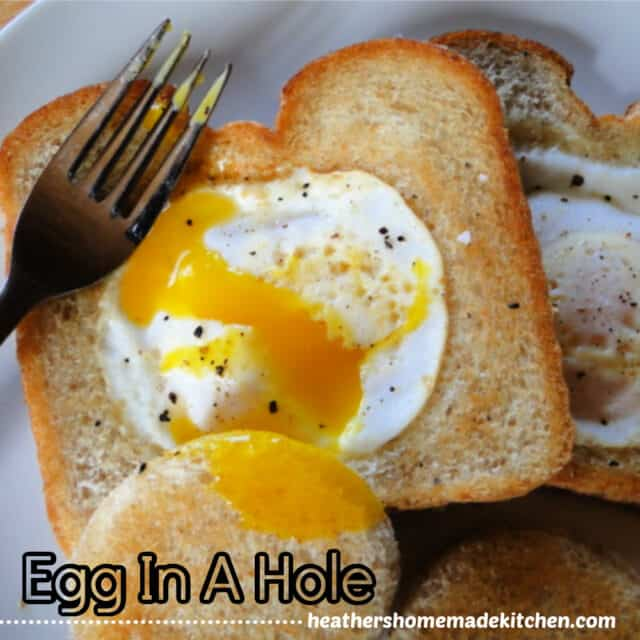 Close up of Egg In A Hole on white round plate with fork and an egg yolk dripping.