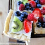 Corner slice of Fresh Fruit Pizza with kiwi, blueberries, strawberries on a cookie crust with cream cheese lemon spread.