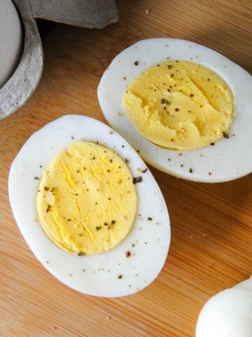 Clos up view of hard boiled egg sliced in half on board next to sliced eggs.