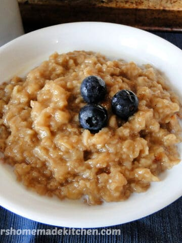 Instant Pot Maple Brown Sugar Oatmeal in white bowl garnished with blueberries on spoon sitting on the side of bowl.