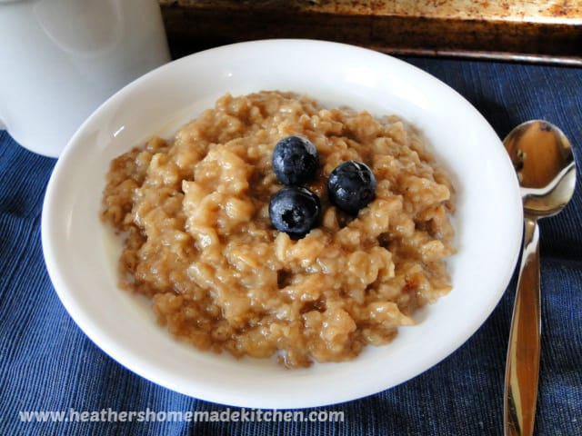 Instant Pot Maple Brown Sugar Oatmeal in white bowl garnished with 3 blueberries and spoon on the side.