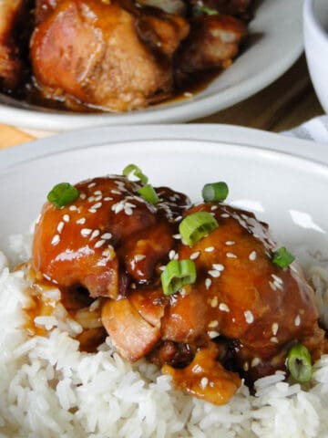 Instant pot teriyaki chicken over white rice in a white serving bowl.