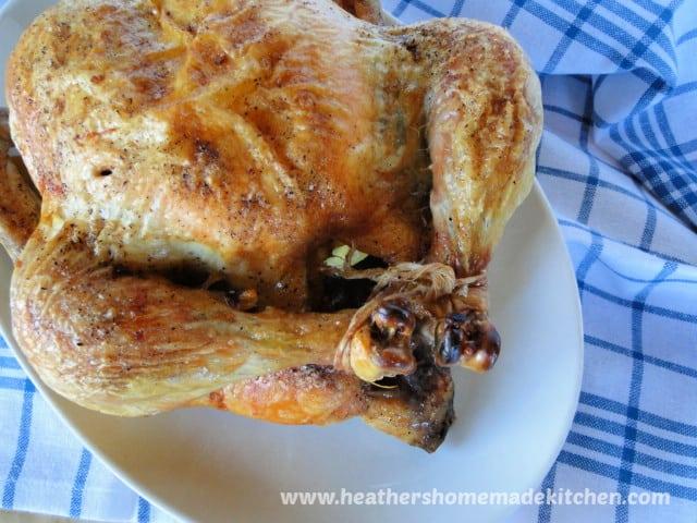 Perfect Roast Chicken legs up on white platter.