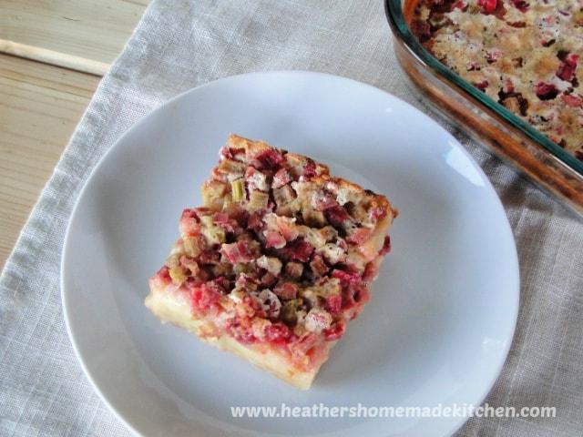 Baking dish of Rhubarb Custard Bars with one slice on white round plate