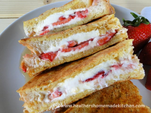 Strawberries & Cream Stuffed French Toast cut in half to show cream cheese and strawberries