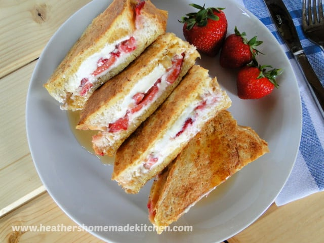 Top view of Strawberries & Cream Stuffed French Toast drizzled with syrup and red strawberries as a garnish.