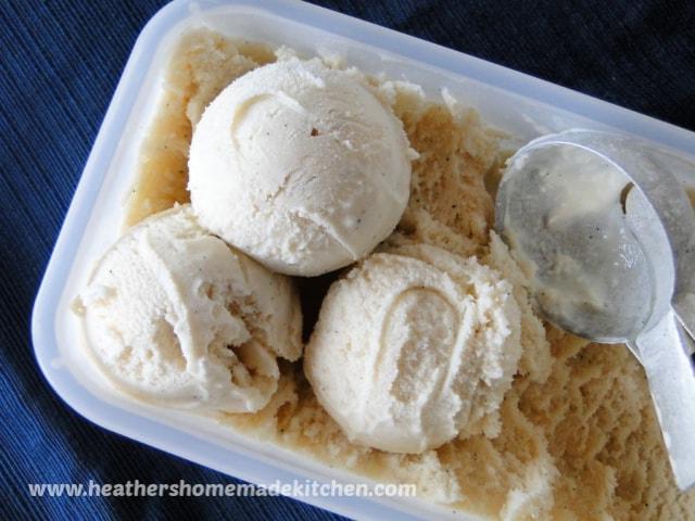 3 scoops Homemade Vanilla Bean Ice Cream in rectangle dish with ice cream scooper.