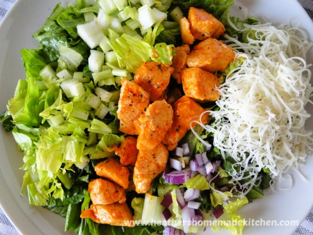 Top view of Buffalo Chicken Salad with celery, red onion and shredded provolone cheese.