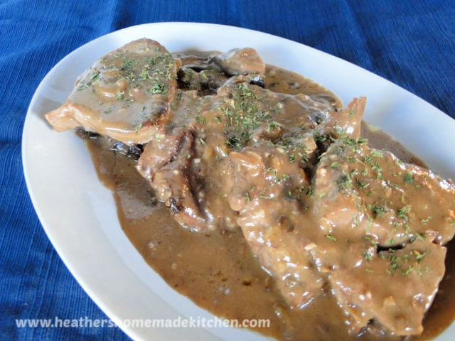 Crock Pot Busy Day Steak on white plate smothered in gravy.
