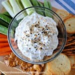 Everything bagel dip surrounded by vegetables and crackers.