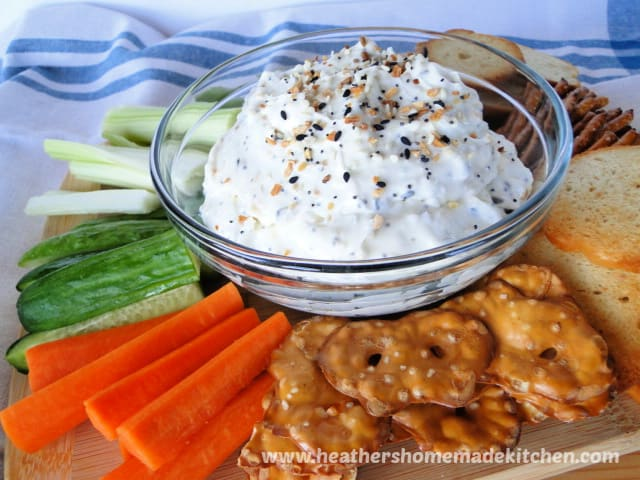 Everything Bagel Dip in clear glass bowl surrounded by vegetables, crackers and pretzels.