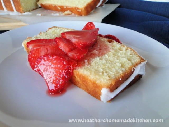 Slice of Glazed lemon pound cake topped with sliced strawberries