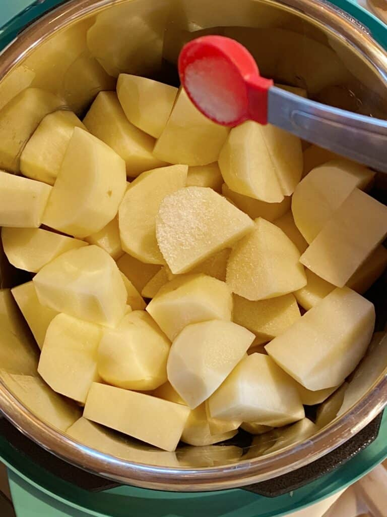 Instant pot with water and raw potatoes, salt being added by a teaspoon.