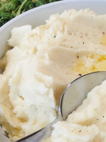 Close up view of instant pot mashed potatoes on spoon in bowl with melted butter on top.