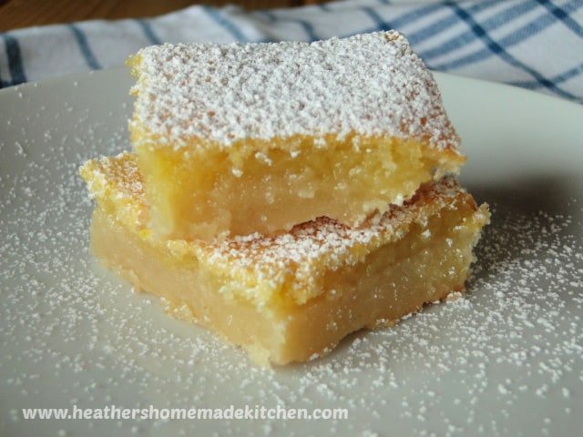 Lemon Bars, 2 stacked on white round plate dusted with powdered sugar.