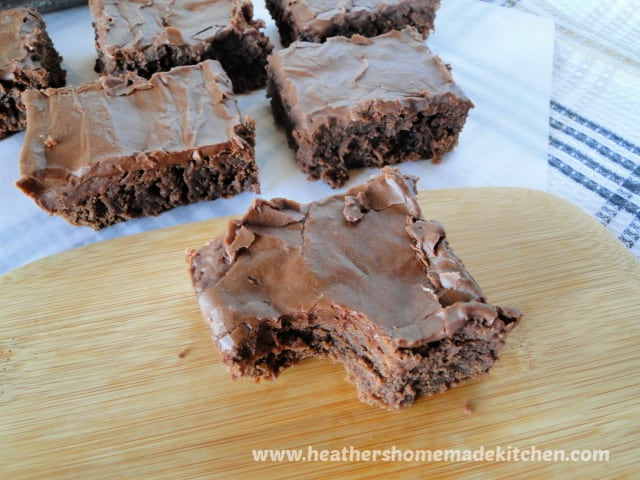 Slices of Old Fashioned Frosted Brownies on board with bite taken out of one slice.