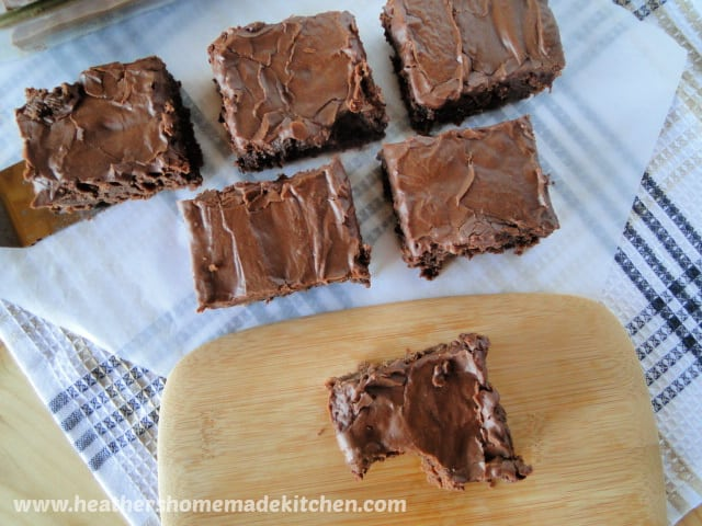 Top View of Old Fashioned Frosted Brownies with one slice on board with bite gone.