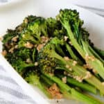 Garlicky Broccolini with bits of garlic in white dish.