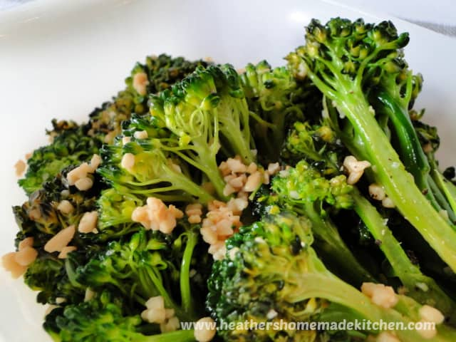 Garlicky Broccolini close up view with bits of garlic.