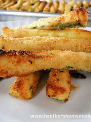 Air Fryer Zucchini Fries in a pile on white plate.