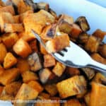 Side angle of air fryer cinnamon cubed sweet potatoes with 3 cubes on a fork.