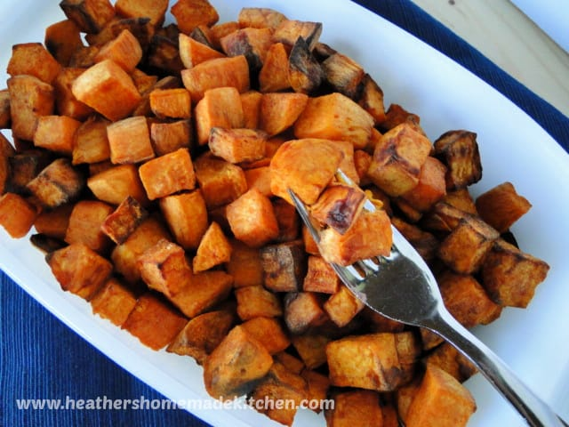 Top view of Air Fryer cubed Cinnamon Sweet Potatoes in white bowl, with 3 cubes on a fork.