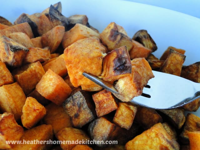 Close up view of Air Fryer Cinnamon cubed Sweet Potatoes with 3 cubes on a fork.